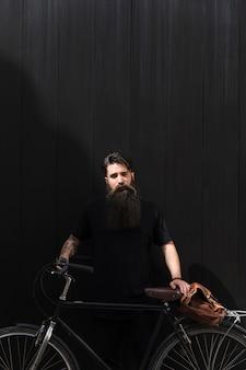 Bel homme debout avec vélo et sac à bandoulière sur fond noir