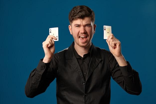 Bel homme, débutant au poker, en gilet noir et chemise. tenant deux cartes à jouer, des as, l'air fou de joie. posant sur fond bleu studio. jeux d'argent, casino. fermer.