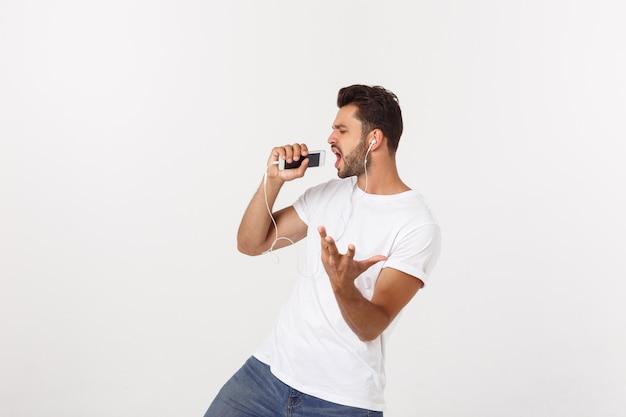 Bel homme décontracté dansant avec téléphone portable isolé sur blanc
