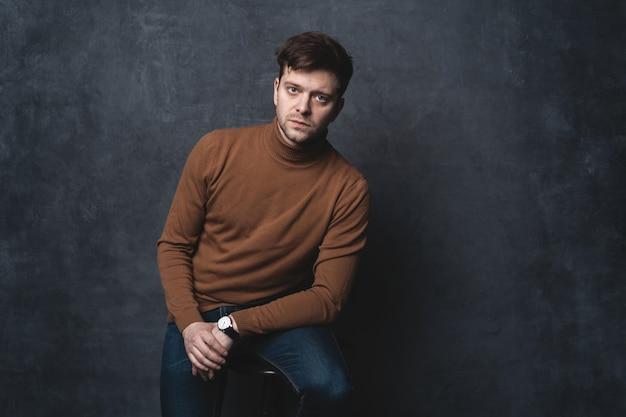 Bel homme décontracté est assis sur une chaise près d'un mur gris foncé et regarde sur le côté.