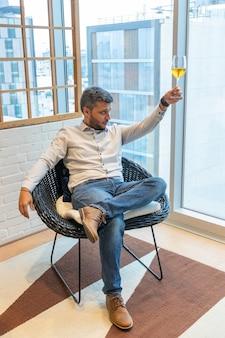 Bel homme dégustant un verre de vin blanc assis dans son salon