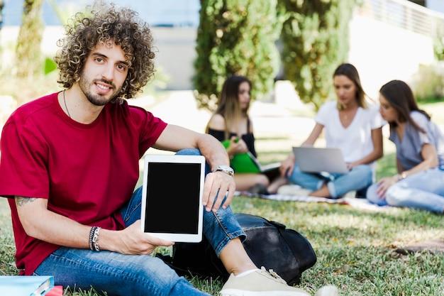 Bel homme démontrant la tablette à la caméra