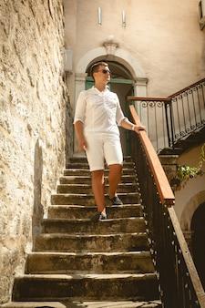 Bel homme descendant le vieil escalier en pierre au jour ensoleillé