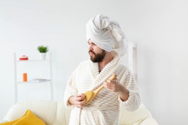Un bel homme drôle fait semblant de jouer sur une brosse de massage comme concept de spa et d'humour amusant pour la guitare