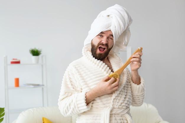 Un bel homme drôle fait semblant de jouer sur une brosse de massage comme une guitare. concept amusant, spa et humour.