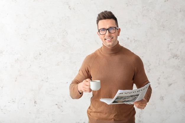 Bel homme avec du café et du journal sur une surface légère