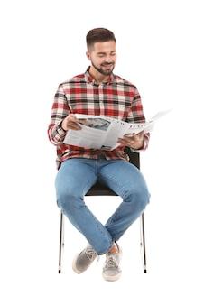 Bel homme avec du journal assis sur une chaise contre le blanc