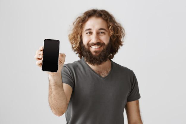 Bel homme du moyen-orient heureux montrant l'écran du smartphone et souriant