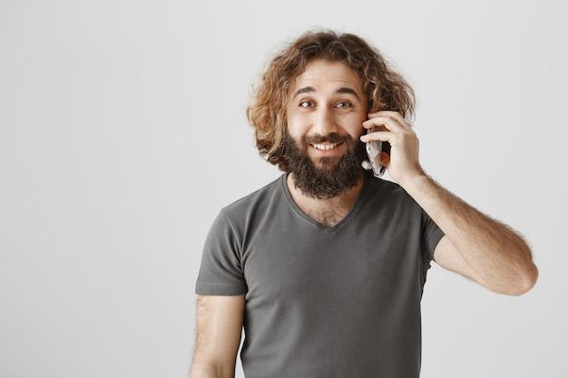Bel homme du moyen-orient parlant au téléphone et souriant