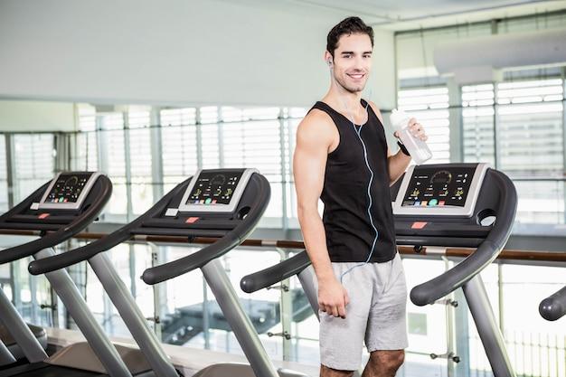 Bel homme sur l'eau potable tapis roulant à la salle de gym