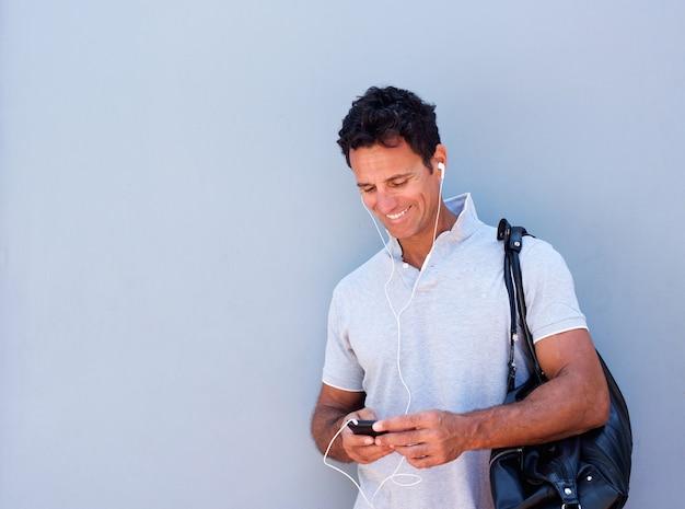 Bel homme écoutant de la musique avec un téléphone mobile