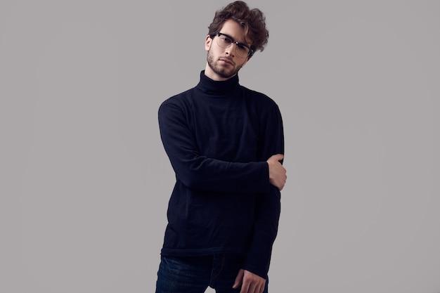 Bel homme élégant aux cheveux bouclés portant col roulé noir et lunettes