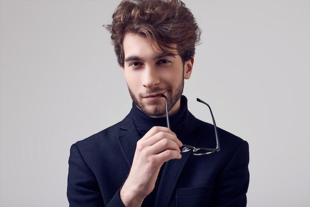 Bel homme élégant aux cheveux bouclés portant costume et lunettes