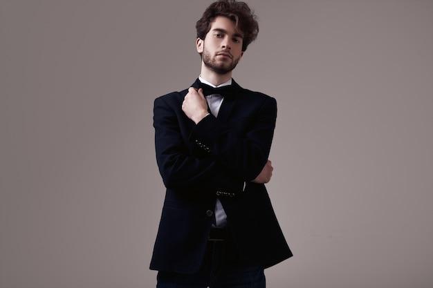Bel homme élégant aux cheveux bouclés portant smoking