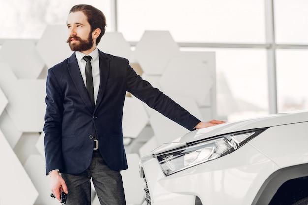 Bel homme élégant dans un salon de l'automobile