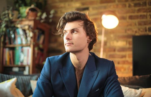 Bel homme élégant vêtu d'une veste bleue, assis sur un canapé