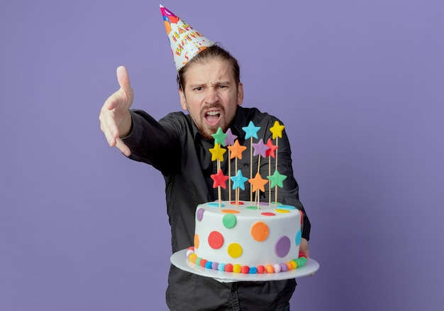 Bel homme ennuyé dans le chapeau d'anniversaire tient le gâteau et pointe vers l'avant avec la main isolée sur le mur violet