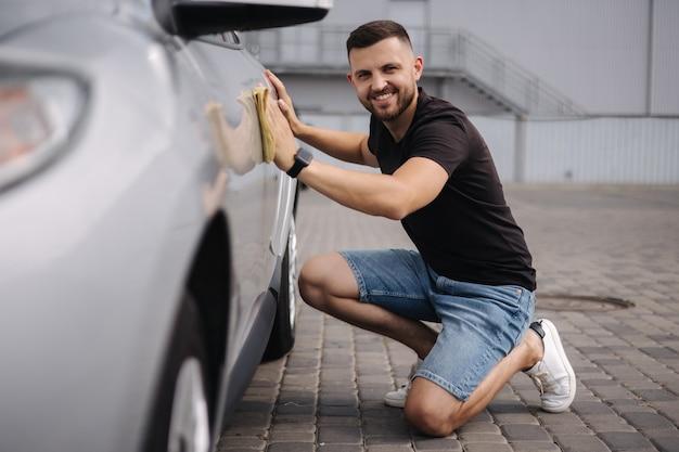 Un bel homme essuie une voiture avec un chiffon dans une salle d'exposition dans une voiture grise de lavage de voiture en libre-service