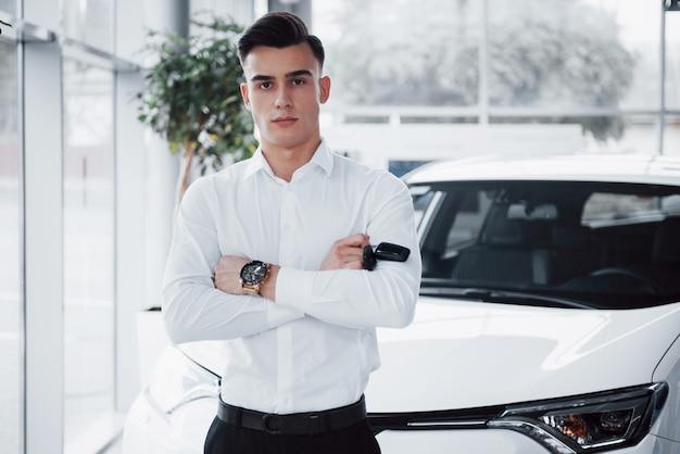 Un bel homme est un acheteur debout à côté d'une nouvelle voiture au centre du concessionnaire et regardant la caméra.