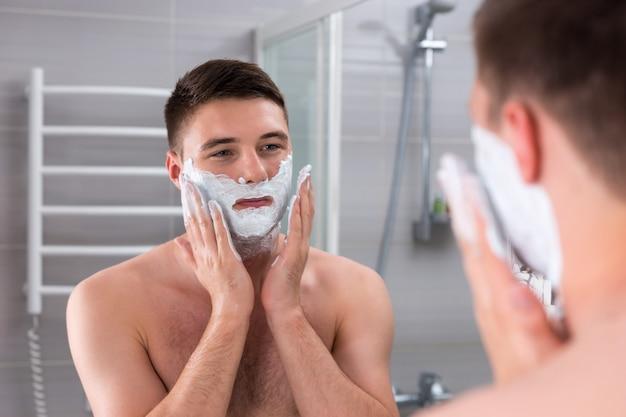 Bel homme étalant du gel à raser sur son visage, debout devant un miroir dans la salle de bains carrelée moderne à la maison
