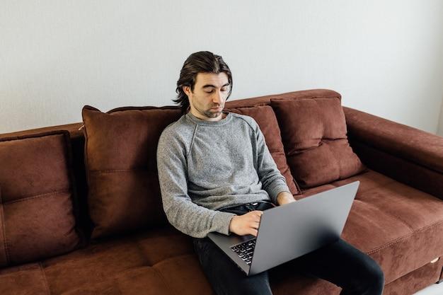 Bel homme étudiant caucasien assis sur un canapé et apprenant avec un ordinateur portable et des livres, fatigué