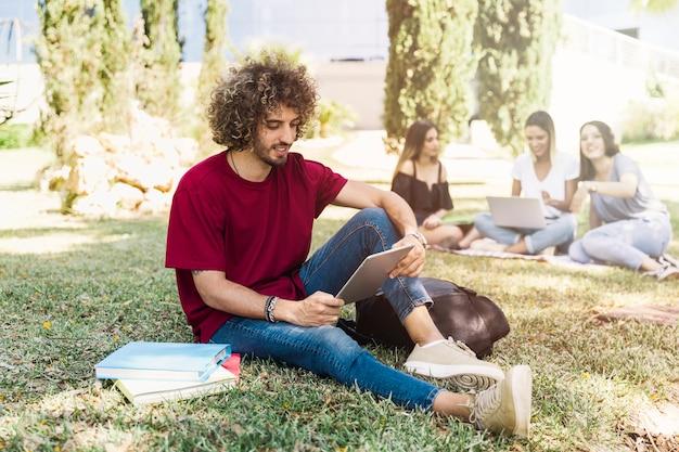 Bel homme étudie avec tablette dans le parc