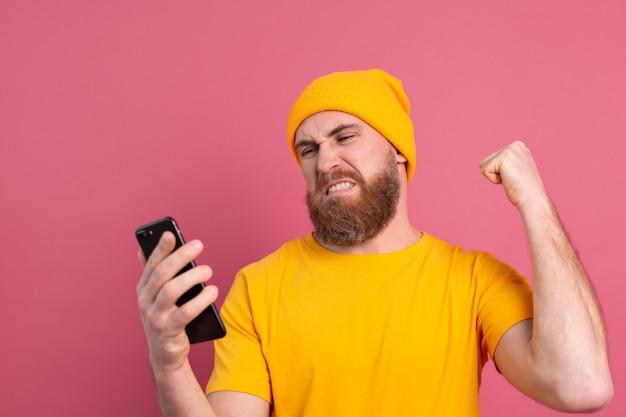 Bel homme européen en colère en colère frappant son téléphone mobile sur rose