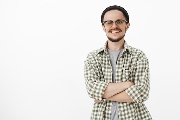 Bel homme européen habile et intelligent avec bonnet noir et chemise verte à carreaux souriant avec une expression sûre de soi et accomplie, souriant largement satisfait du travail bien fait