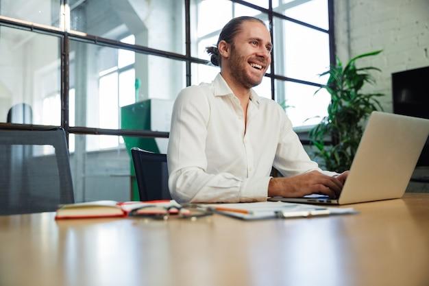 Bel homme excité riant et travaillant avec un ordinateur portable assis à table dans un bureau moderne