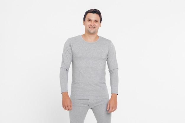 Bel homme exhibe des vêtements gris sur fond blanc