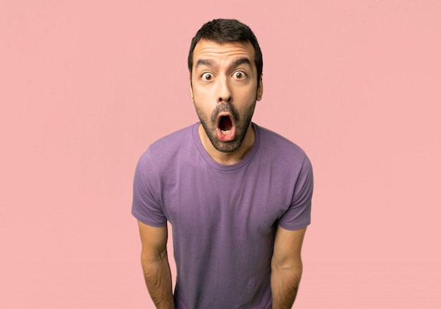 Bel homme avec une expression faciale surprise et choquée sur fond rose isolé