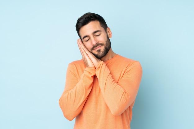 Bel homme faisant le geste du sommeil dans une expression dorable sur bleu