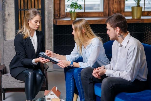Bel homme et femme assise sur l'entraîneur pendant que la femme signe le contrat d'achat d'une nouvelle maison, appartement.