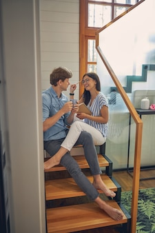 Bel homme et femme joyeuse assis sur les escaliers en bois tout en s'amusant dans la maison moderne de luxe