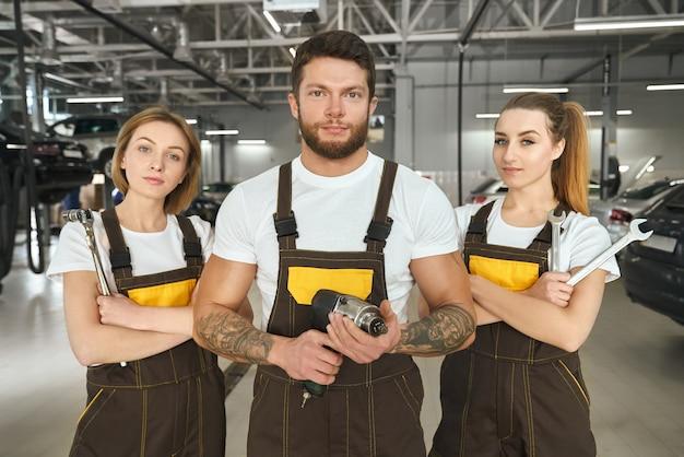 Bel homme et femmes mécaniciens de pose de services automatiques.
