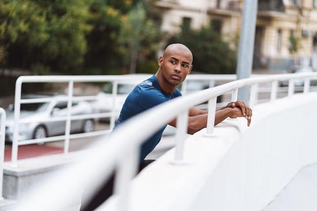 Bel homme de fitness africain en forme de repos après l'entraînement à l'extérieur, s'appuyant sur le rail