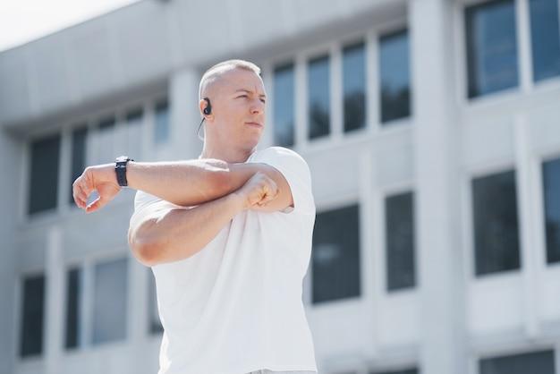 Un bel homme de fitness dans un vêtement de sport, faisant des étirements tout en se préparant à un exercice sérieux dans la ville moderne