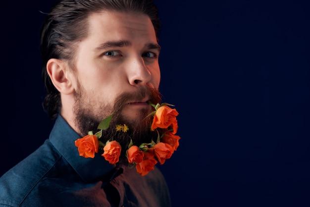 Bel homme avec des fleurs dans une barbe dans un studio de gros plan de chemise noire