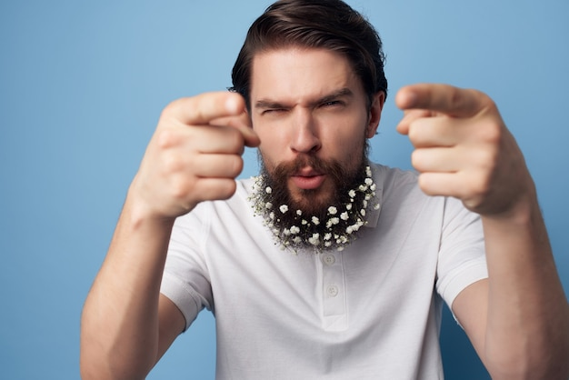 Bel homme avec des fleurs dans les émotions de soins des cheveux barbe fond isolé