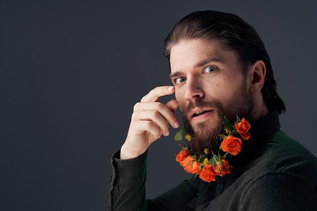 Bel homme fleurs dans une romance de décoration barbe sombre.