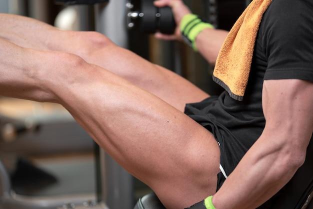 Bel homme fort effectué séance d'entraînement de presse jambe dans la salle de gym.