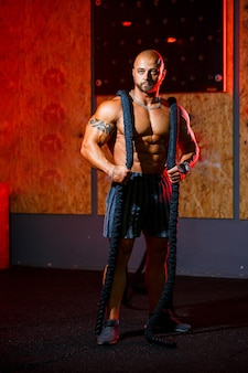 Bel homme fort sportif posant avec une corde de sport sur le fond de la salle de gym. un bodybuilder fort avec des abdominaux, des épaules, des biceps, des triceps et une poitrine parfaits.