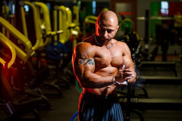 Bel homme fort sportif posant sur le fond de la salle de gym. un bodybuilder fort avec des abdominaux, des épaules, des biceps, des triceps et une poitrine parfaits.