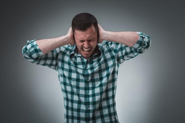 Bel homme frustré couvrant ses oreilles avec les mains debout sur fond gris.