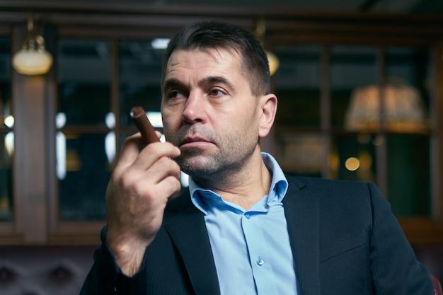 Bel homme fumant un cigare dans un bar-salon