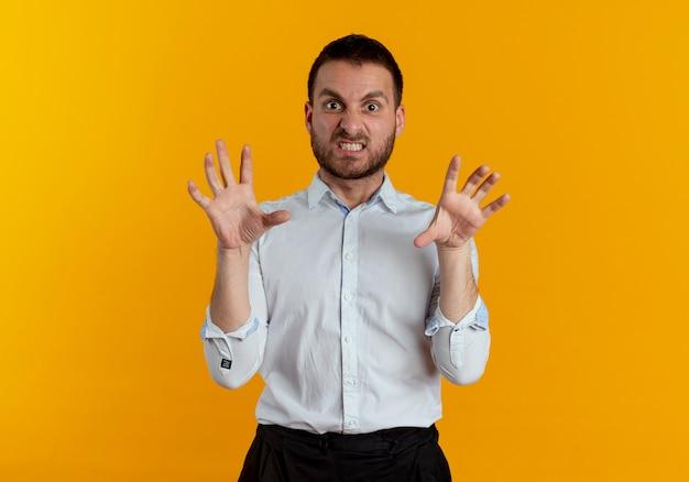 Bel homme furieux serre les doigts isolés sur un mur orange