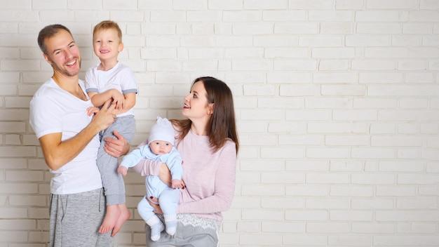 Bel homme avec garçon mignon et femme charmante avec adorable bébé debout près de mur de briques blanches