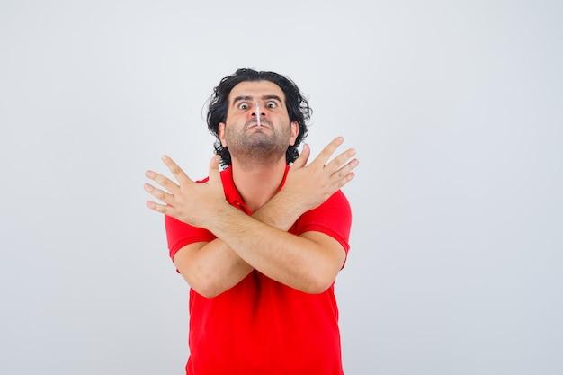 Bel homme gardant la cigarette dans la bouche, tenant deux bras croisés, gesticulant signe x en t-shirt rouge et à la colère