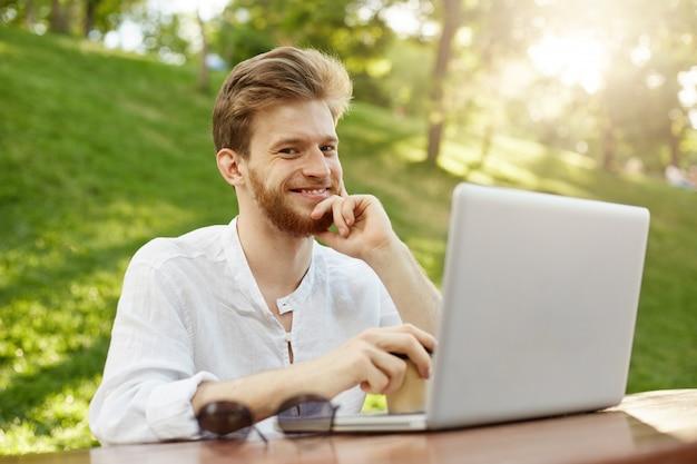 Bel homme gingembre mature avec ordinateur portable dans le parc
