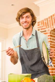 Bel homme goûter la préparation dans la cuisine